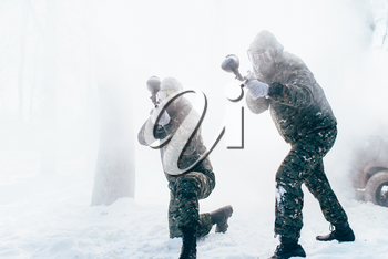 Two paintball players in uniform and masks shooting at the enemy, side view, winter forest battle. Extreme game