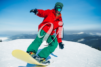 Snowboarder in glasses poses with board in hands, blue sky and snowy mountains on background. Winter active sport, extreme lifestyle, snowboarding