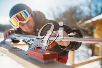 Male skier checks skis before skiing, closeup. Winter active sport, extreme lifestyle. Downhill skiing