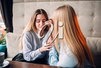 Young woman calms her girlfriend in cafe. Female friends leisures in restaurant, gossipers meeting