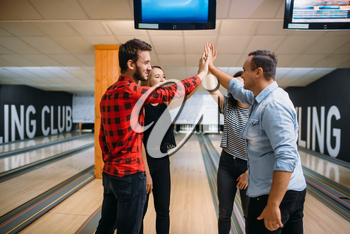 Bowling team joined hands before the competition. Players before strike. Friends playing classical tenpin game in club, active people