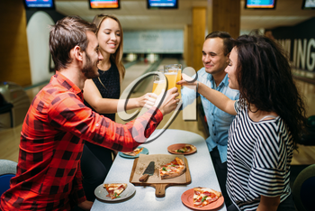 Friends drinks juice and eats pizza in bowling club, active leisure, healthy lifestyle, bowling game