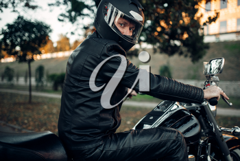 Biker in helmet poses on a motorcycle, classical chopper. Vintage bike, rider and his two-wheeled friend, freedom lifestyle, biking