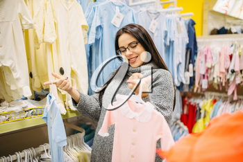 Woman choosing clothes in the store for newborns. Future mother in shop of goods for infants