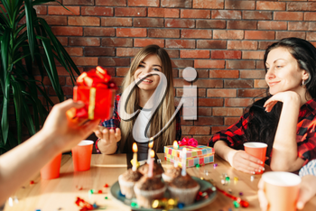 Group of highschool students give each other gifts. Youth at the table in the flat, home party, birthday celebration