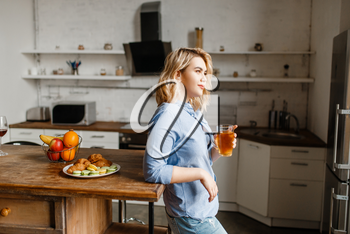 Young woman having breakfast with croissants and cookies. Female person eats dessert on the kitchen, good morning, happy lifestyle