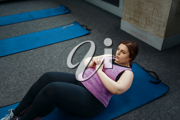 Overweight woman doing exercise on mat in gym, active training. Obese female person struggles with excess weight, aerobic workout against obesity, sport club