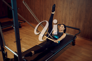 Sporty woman in sportswear doing stretching pilates exercise in gym. Fitness workuot in sport club. Athletic female person, aerobics