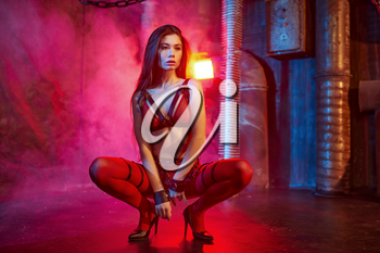 Sexy model in red bdsm suit and handcuffs, abandoned factory interior on background. Young girl in erotic underwear, sex fetish, sexual fantasy