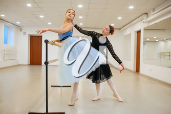 Master rehearsing with young ballerina in class. Ballet school, female dancers on choreography lesson, girls practicing grace dance