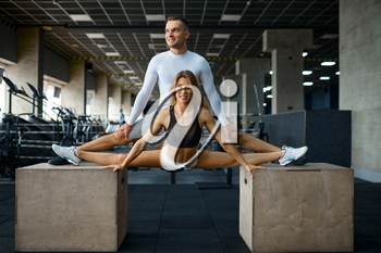 Slim couple doing stretching exercise on cubes in gym. Athletic man and woman on workout in sport club, active healthy lifestyle, physical wellness