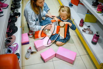 Mother and little baby opens box with shoes in kid's store. Mom and adorable girl near the showcase in children's shop, happy childhood, family makes a purchase in market