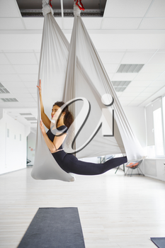 Aerial yoga, slim woman poses on hammock. Fitness, pilates and dance exercises mix. Female person on yogi workout in sports studio