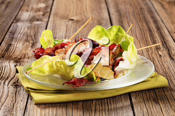 Grilled chicken skewers and bacon served on lettuce leaves