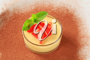 Small dish of custard topped with strawberry