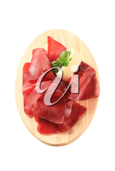 Thin slices of dried meat on a cutting board