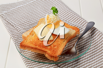 Two pieces of crispy toast, butter and boiled egg