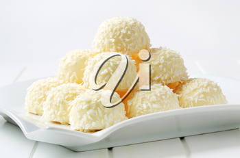 Pile of coconut snowball truffles on square plate