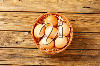 Fresh brown eggs in terracotta bowl on wooden table