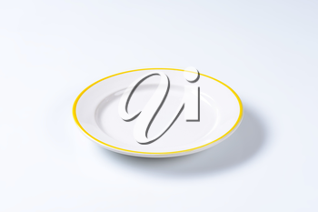 Rimmed dinner plate with yellow colored edge
