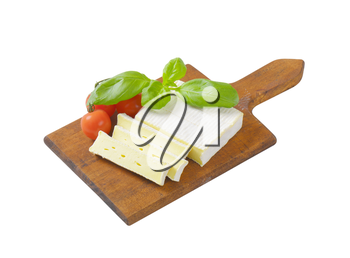 Sliced soft cow's milk cheese on cutting board