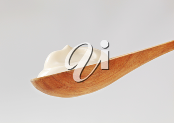 Fresh white cream on a  small deep wooden spoon