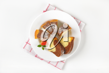sliced marble bundt cake on white plate and checkered dish towel