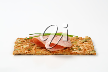 pumpkin seed cracker with thin slices of soft sausage