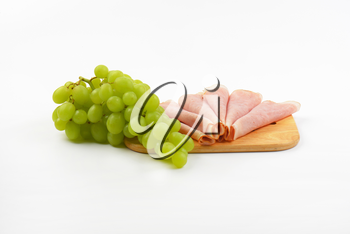 slices of ham and bunch of white grapes on wooden cutting board
