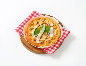 apple tart on checked red dishtowel and round cutting board