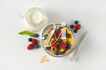 bowl of mixed breakfast cereals with fresh raspberries and blueberries, and jug of milk