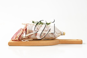 sliced dry cured sausage on wooden cutting board