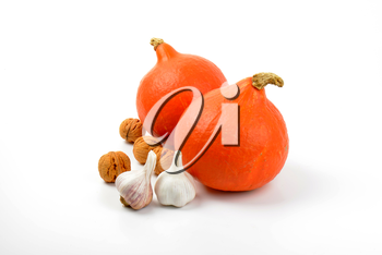 two orange pumpkins with garlic and walnuts on white background