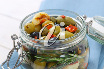 jar of pickled olives, capers, caper berries and garlic