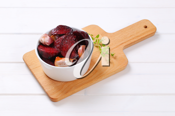 bowl of baked beetroot with garlic and thyme on wooden cutting board