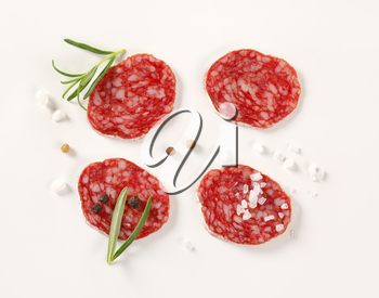 slices of French dry cured salami with spices on white background