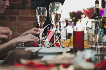 Hands with glasses over a festive table.