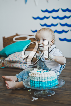 Babe sits and eats cake with his hands.