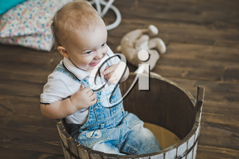 Little one-year-old child is seated in a wooden basin.