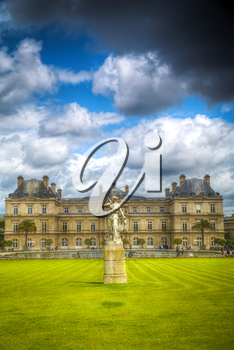 Luxembourg gardens and palace with puffy clouds in Paris, France