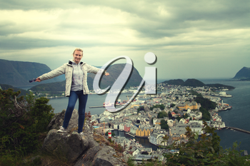 girl standing on a mountain overlooking the city and the ocean. View from Mount Aksla in Alesund, Norway.