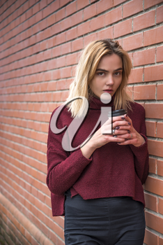 girl with a glass of coffee near a brick wall
