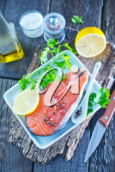 raw salmon on the white plate and on a table