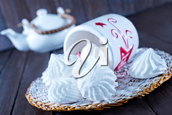 meringues in bowl and on a table