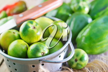 green tomato and pepper on the wooden table