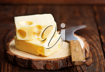 cheese and knife on wooden board and on a table