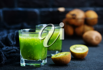 kiwi smoothie in glass and on a table