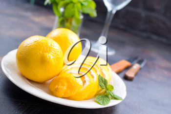 fresh lemons with mint leaves on a table