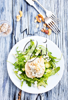 Salad with green arugula plant, pear and cottage cheese