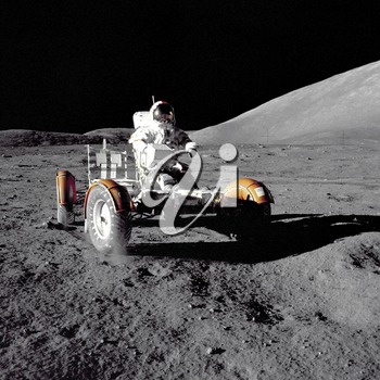 Royalty Free Photo of an Astronaut Driving the Rover on the Moon